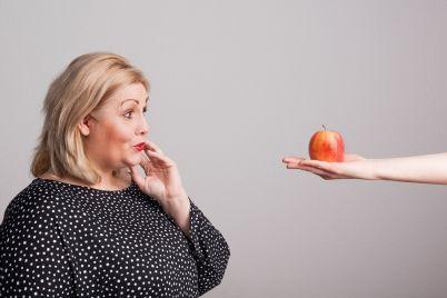 a-female-hand-giving-an-apple-to-an-attractive-A2K8LMC.jpg