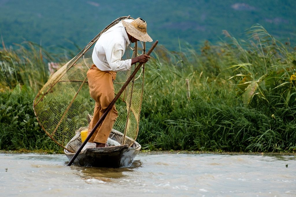 asian-fisherman-with-the-net-on-a-boat-inle-lake-PNYKZK8.jpg