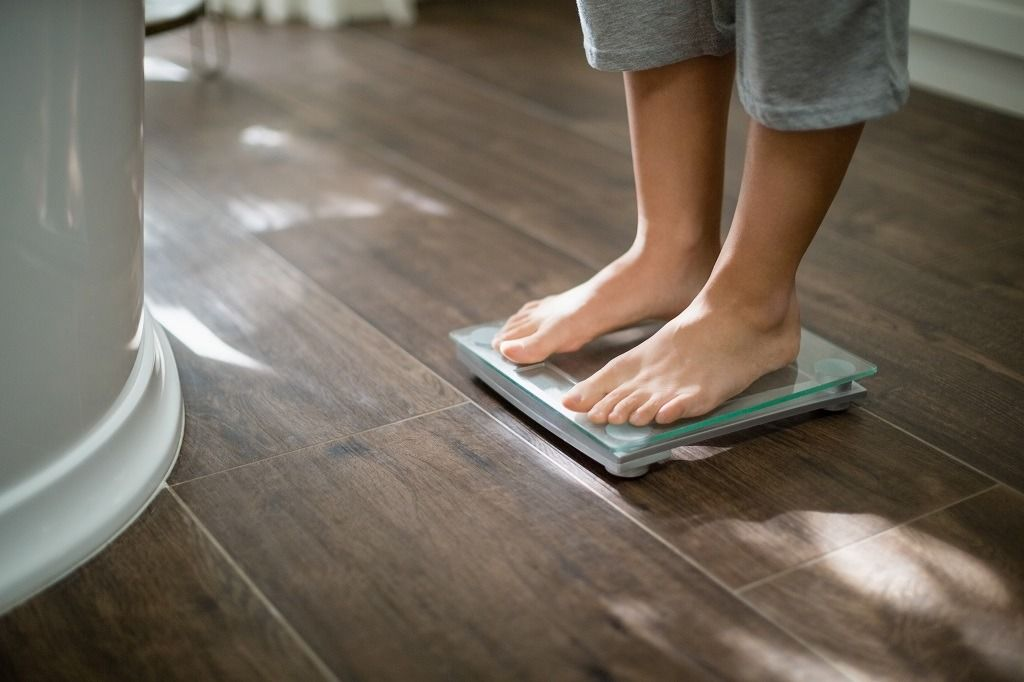 boy-checking-his-weight-on-weight-scale-FHMQAD9.jpg