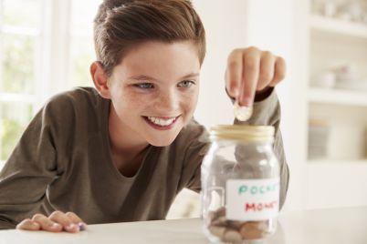 boy-saving-pocket-money-in-glass-jar-at-home-PXW6UN9.jpg