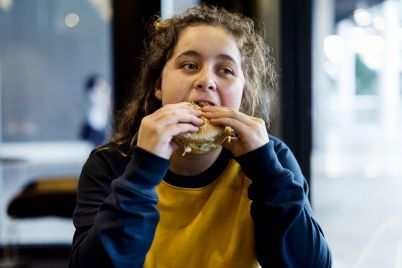 close-up-of-teenage-girl-eating-hamburger-obesity.jpg