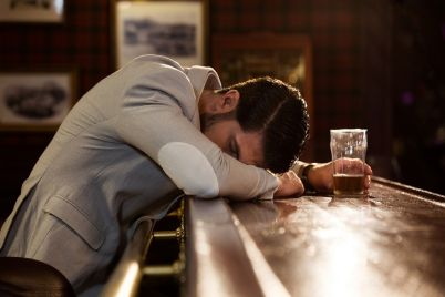 drunk-man-sleeping-on-a-pub-counter-PZB7S5Y.jpg