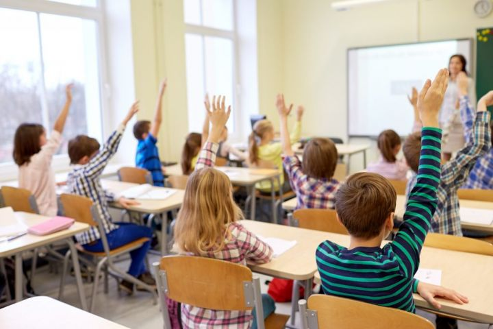 group-of-school-kids-raising-hands-in-classroom-PF36XQ9-e1564577394792.jpg