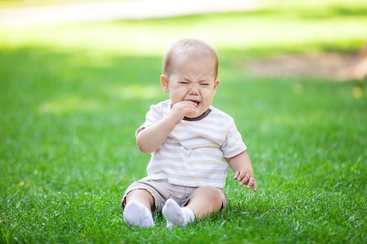 little-boy-crying-while-sitting-on-grass-in-park-PYA3WDY.jpg