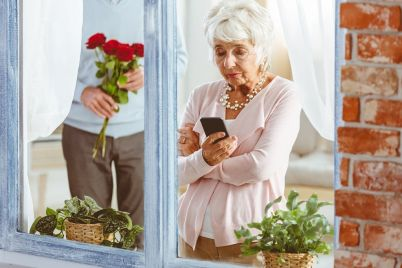 man-surprising-woman-looking-at-telephone-PP4V9U3.jpg