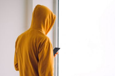man-with-hoodie-and-mobile-phone-standing-by-the-PY9XD6K.jpg