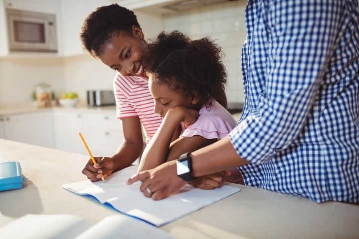 parents-assisting-daughter-with-homework-NRH6UEL.jpg