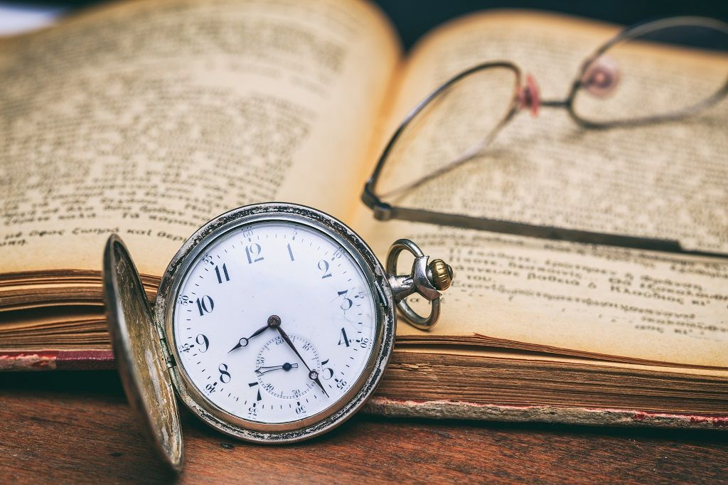 pocket-watch-and-eye-glasses-on-an-old-book-PEZN6FM.jpg