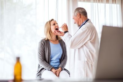 senior-doctor-examining-a-young-woman-in-office-P7L2X9C.jpg