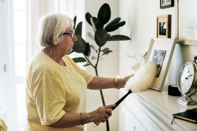 senior-woman-dusting-a-family-photo-PHX7DFU.jpg
