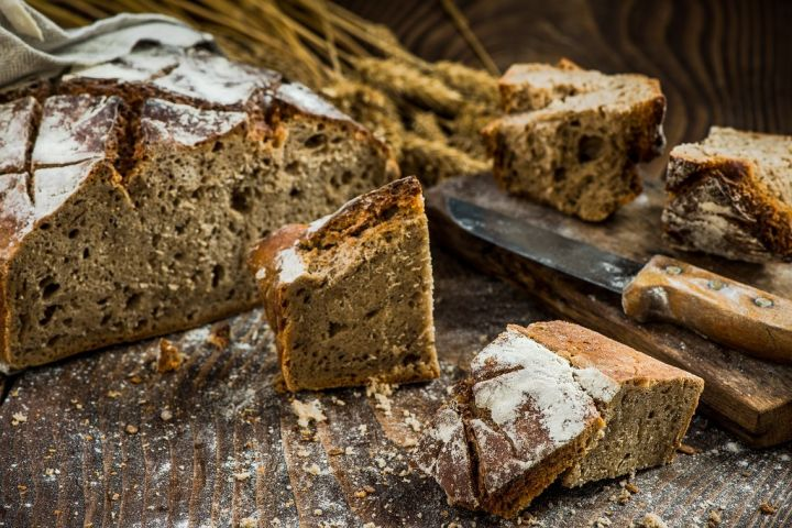 sharing-pieces-of-freshly-baked-bread-loaf-P8JGYCF.jpg