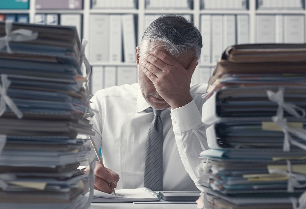 stressed-business-executive-and-piles-of-PX89VUH.jpg