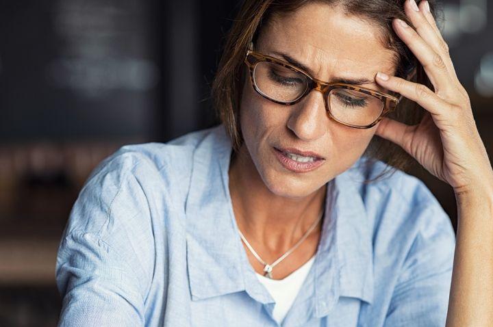 stressed-woman-wearing-eyeglasses-RP6QLAS.jpg