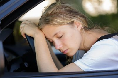 tired-woman-sleep-in-car-PUUYKMT.jpg