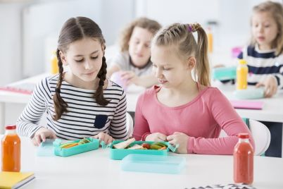 two-young-girls-during-snack-time-in-a-school-KSZXLF3.jpg