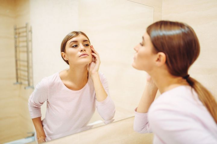 woman-looking-on-face-at-the-mirror-in-bathroom-KVQPJCT.jpg