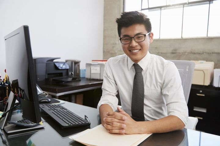 young-asian-male-professional-at-desk-smiling-to-RU9HW36-e1564404185192.jpg