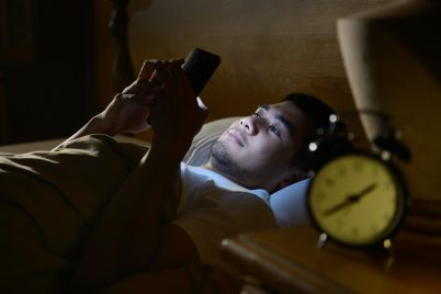 young-man-using-a-smartphone-in-his-bed-at-night-P88RXTS.jpg
